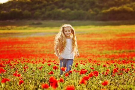 girl running in field of red poppies