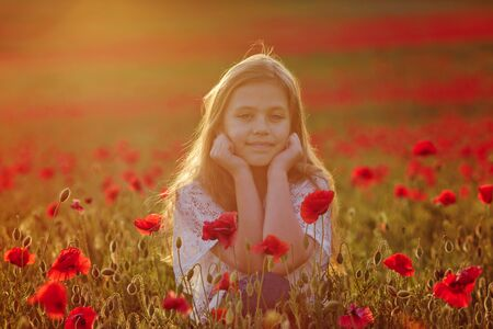 little girl in popply field at sunset time Archivio Fotografico