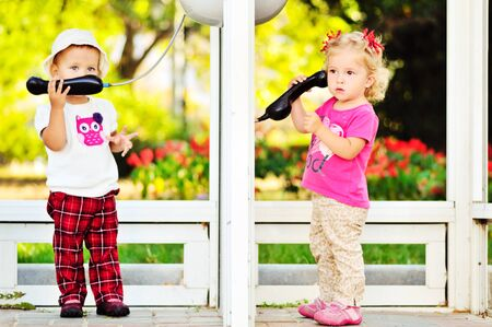 toddler girls talking by the city phones
