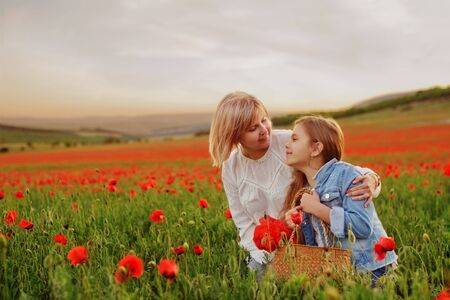 happy mother and daughter in the poppy field