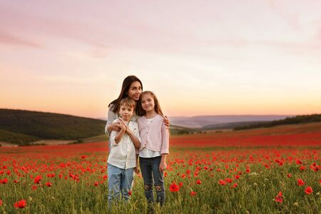 Mother, son and daughter in the field of red poppies
