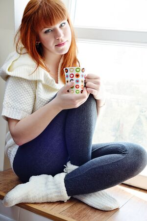 redhead woman at home with cup of tea near the window