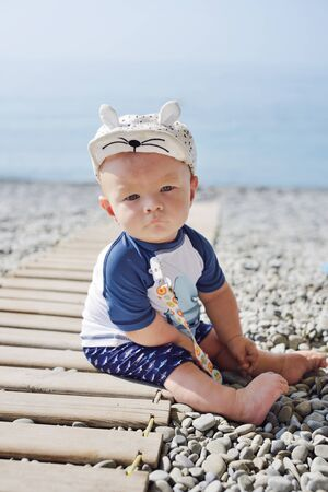 Little baby boy wearing  UV and sun protection  suit  on the beach. Archivio Fotografico