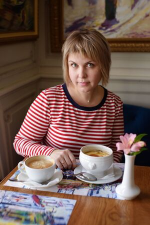 woman in cafe drinking coffee and eating soup