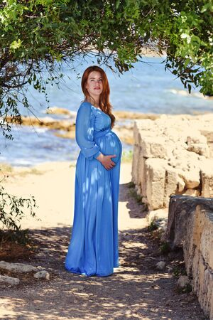 pregnant redhead woman walking near the sea Archivio Fotografico