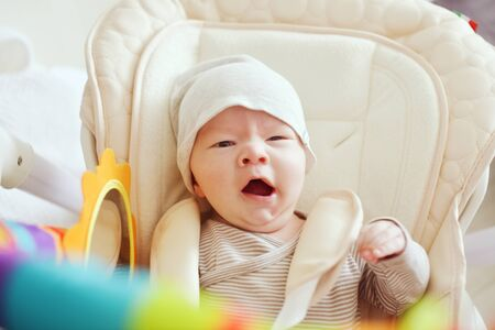 yawning newborn baby is laying in the chair