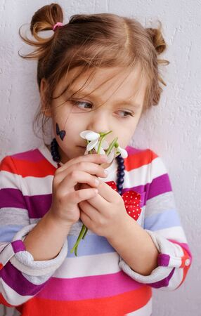 little sweet girl smelling flowers of spring