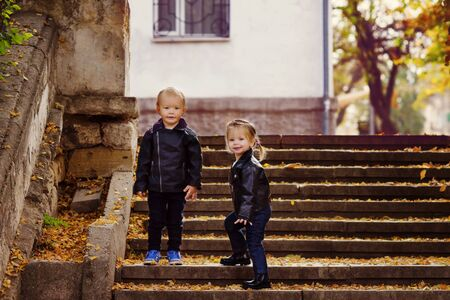 two fashion toddler sibling on the walk in fall time