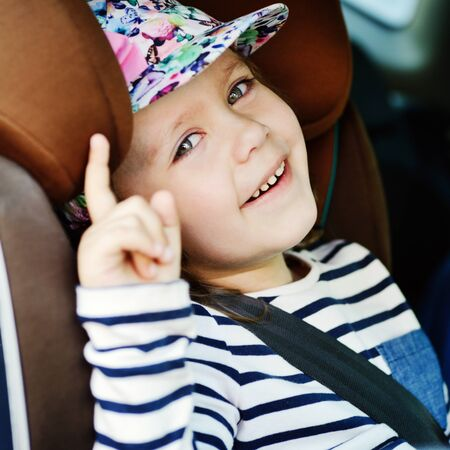 transport, safety, road trip and childhood concept -  happy little girl sitting in car seat