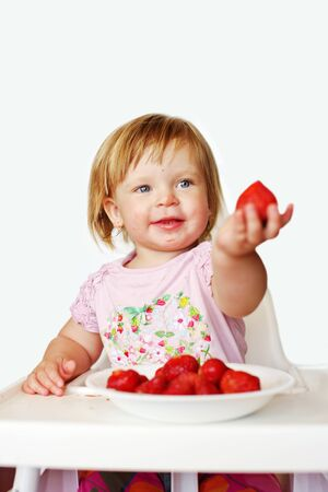happy baby  girl with dirty face eating strawberry  Archivio Fotografico