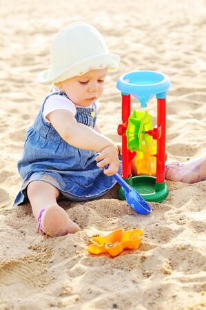 Cute toddler girl playing in sand  outdoor