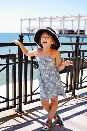Beautiful little girl on the beach enjoying summer vacation