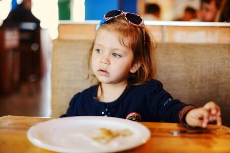 pensive pretty toddler girl sitting  in  the cafe Archivio Fotografico
