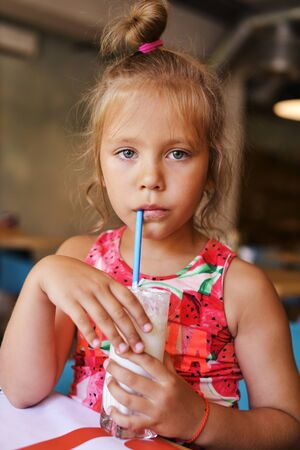 little girl is drinking a milkshake in cafe Archivio Fotografico