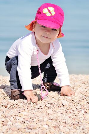 funny baby girl playing near the sea Archivio Fotografico