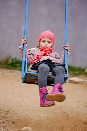 Happy cute child girl on swing in fall Archivio Fotografico