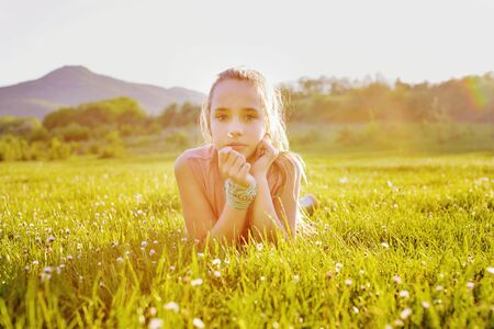 teen girl on the sunny meadow in backlit Archivio Fotografico - 150505440