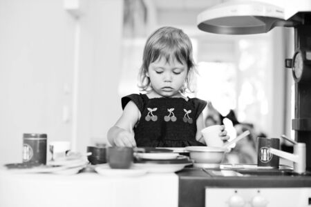serious toddler girl is playing toy kitchen Archivio Fotografico