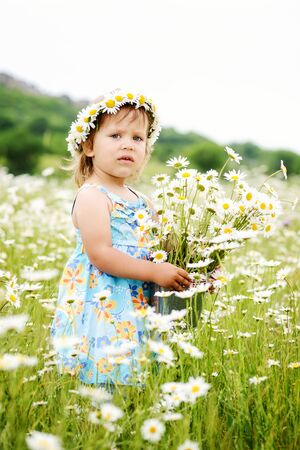 funny   toddler girl in a daisy field wearing wreath Archivio Fotografico
