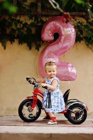 birthday of toddler girl and her new bicycle