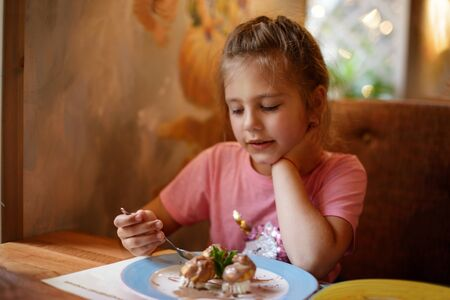 child girl in a cafe eating a dessert Archivio Fotografico