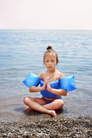 Little cute girl meditates in turkish pose in  the sea Archivio Fotografico