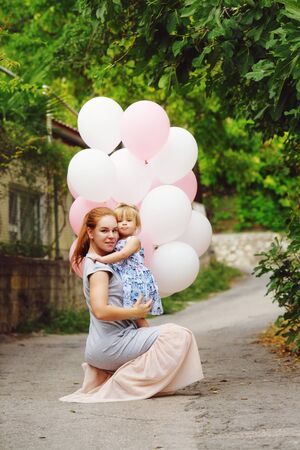 Happy young woman and her little daughters with ballons outdoors Archivio Fotografico