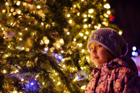 little girl standing near the christmas tree in new year city Archivio Fotografico