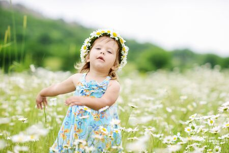 funny dancing toddler girl  in a daisy field