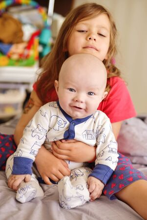 baby boy with sister on the bed