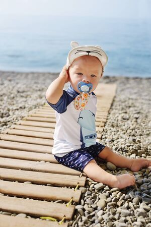 funny little baby boy on the beach wearing UV and sun   protective swim suit