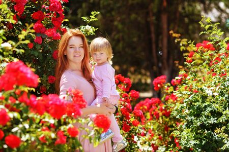happy family in the blossom roses garden Archivio Fotografico