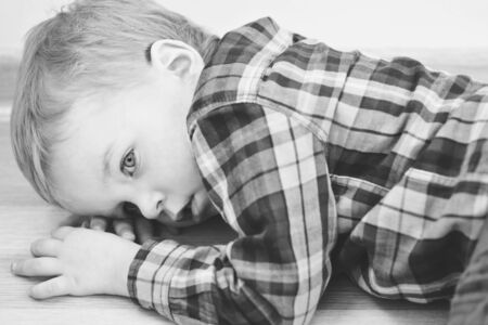 Portrait of a cute little boy lying on floor