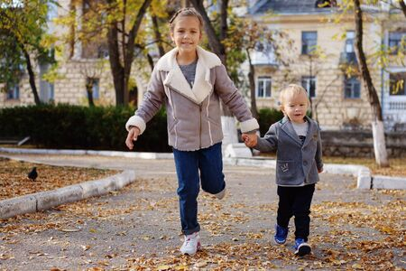 sister and toddler brother running in the fall park, focus on the brothers face