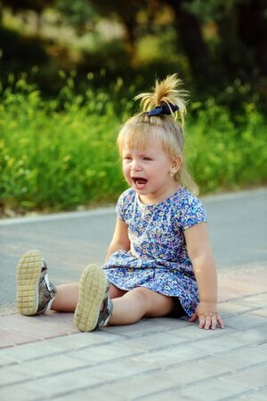 a crying little funny toddler girl outdoors Archivio Fotografico