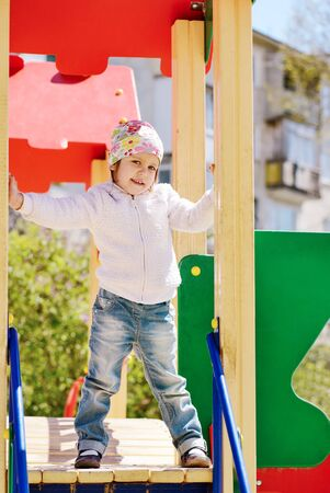 happy toddler girl climbing on the playground