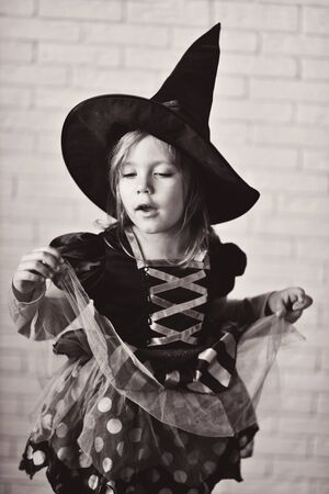 Portrait of girl wearing witch costume posing before camera Archivio Fotografico