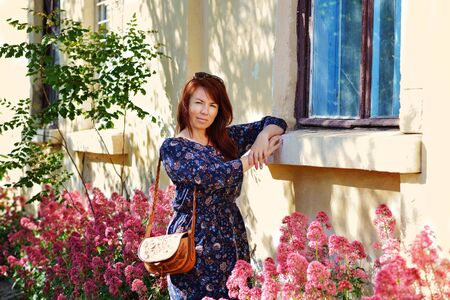 redhead woman in spring time near the house