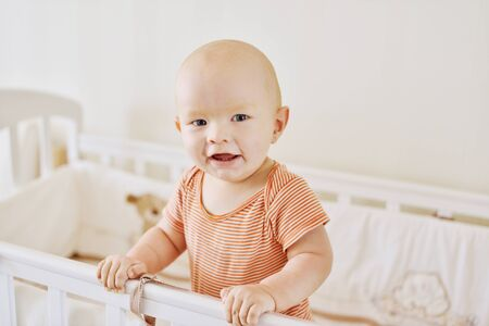 happy and funny baby boy standing in the bed Archivio Fotografico