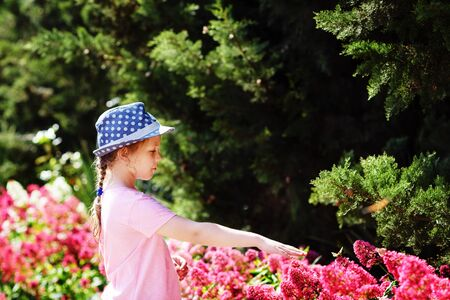 Child want to touch  butterfly in the summergarden. Archivio Fotografico