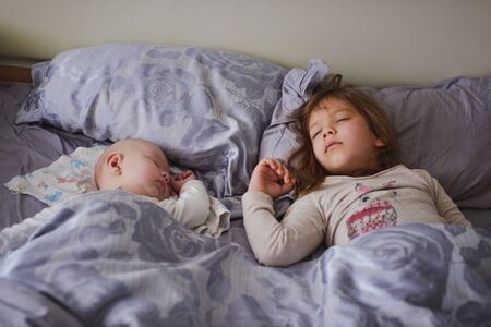 Lovely baby brother and toddler sister sleeping in parents bed at home, soft focus