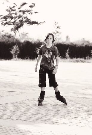 preteen boy wearing roller skates playing  outdoors Archivio Fotografico
