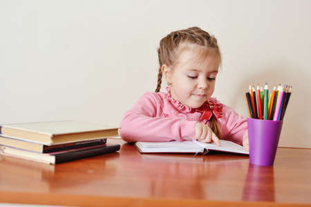Child girl learning reading  book at the table