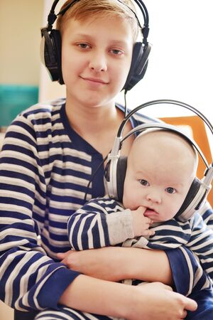 teen boy and his baby brother wearing headphones at home Archivio Fotografico