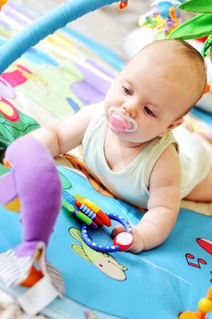 a baby on the carpet with toys