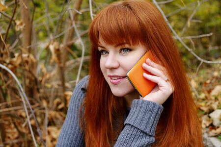 redhead young woman with mobile phone outdoors Archivio Fotografico