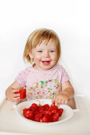 happy baby  girl eating strawberry with dirty face