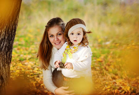 happy mother and baby daughter in fall time