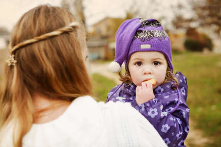 toddler girl on mothers hands eating biscuit in fall