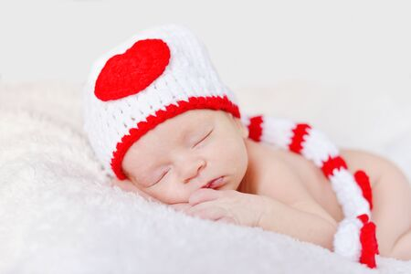 Newborn baby sleeping and wearing a knitted hat